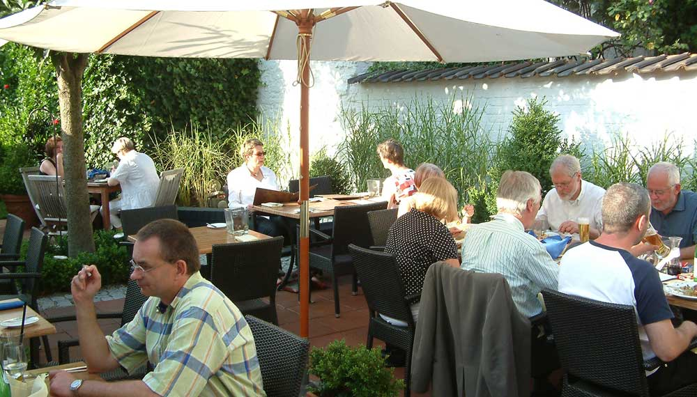 Gasten aan een tafeltje in de tuin van een restaurant