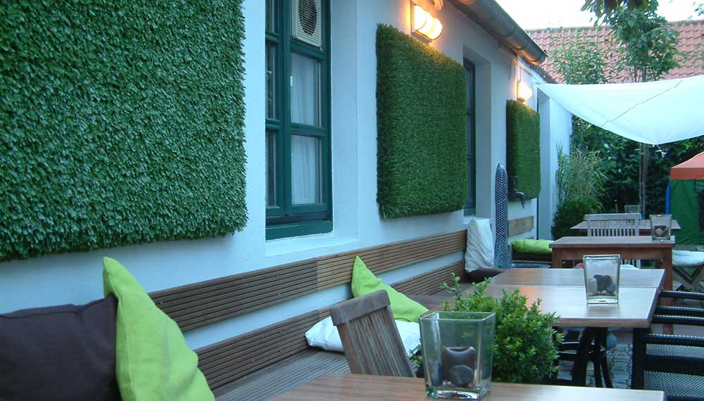 kunstgraspanelen aan de wand van restauranttuin