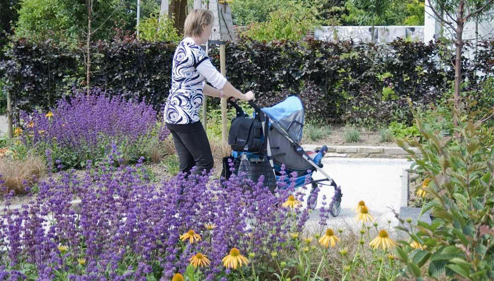 vrouw met kinderwagen in expositietuin
