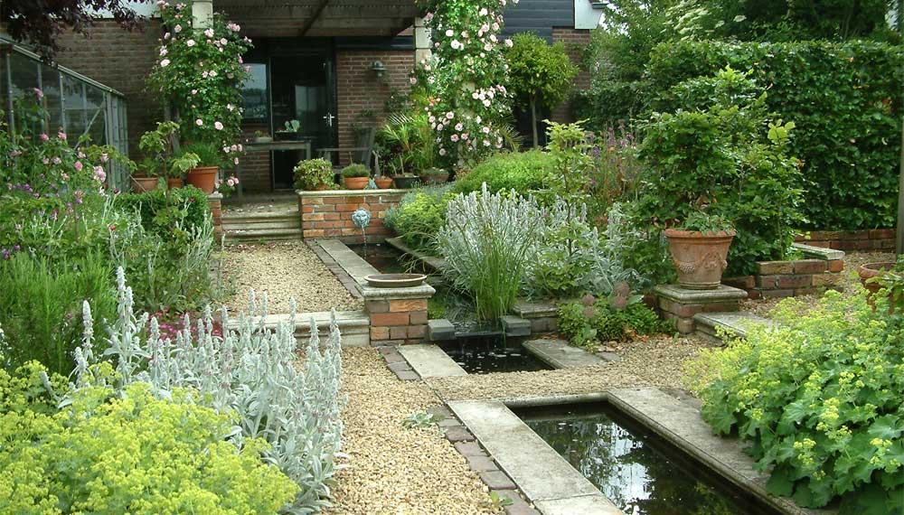 tuin met canal en weelderige beplanting